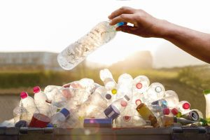 A hand putting a plastic bottle in the plastic bottle recycling