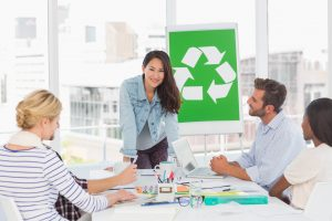 A team of people chatting in an office about recycling