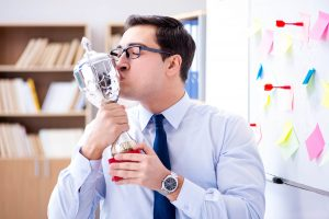 A man kissing a recycling award cup