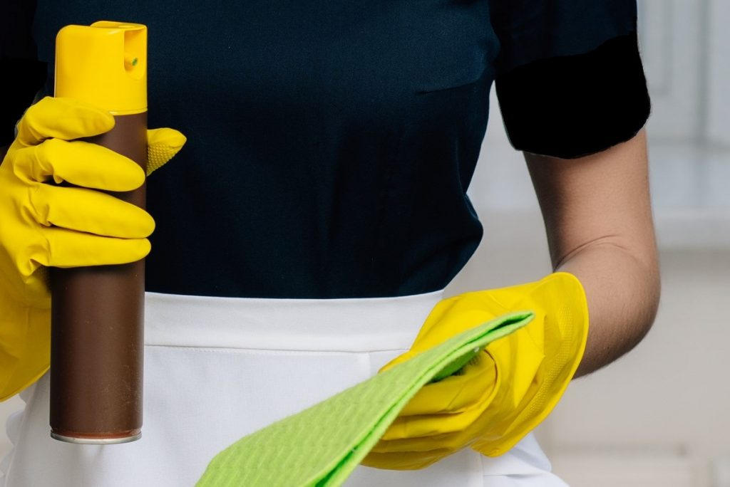 Someone wearing rubber gloves about to spray cleaning product from an aerosol can into a cloth