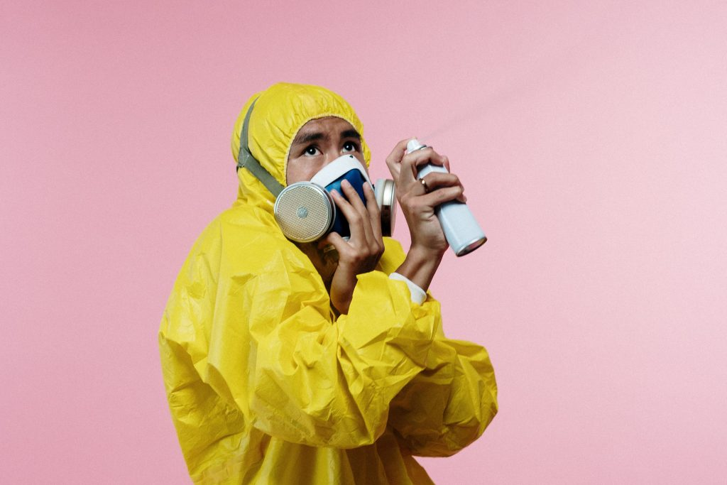 Person in hazmat suit and mask spraying an aerosol can in the air