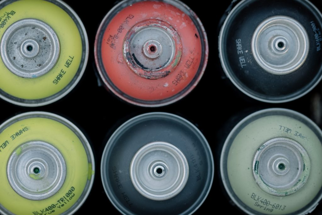 Aerosol spray cans with the nozzle removed.