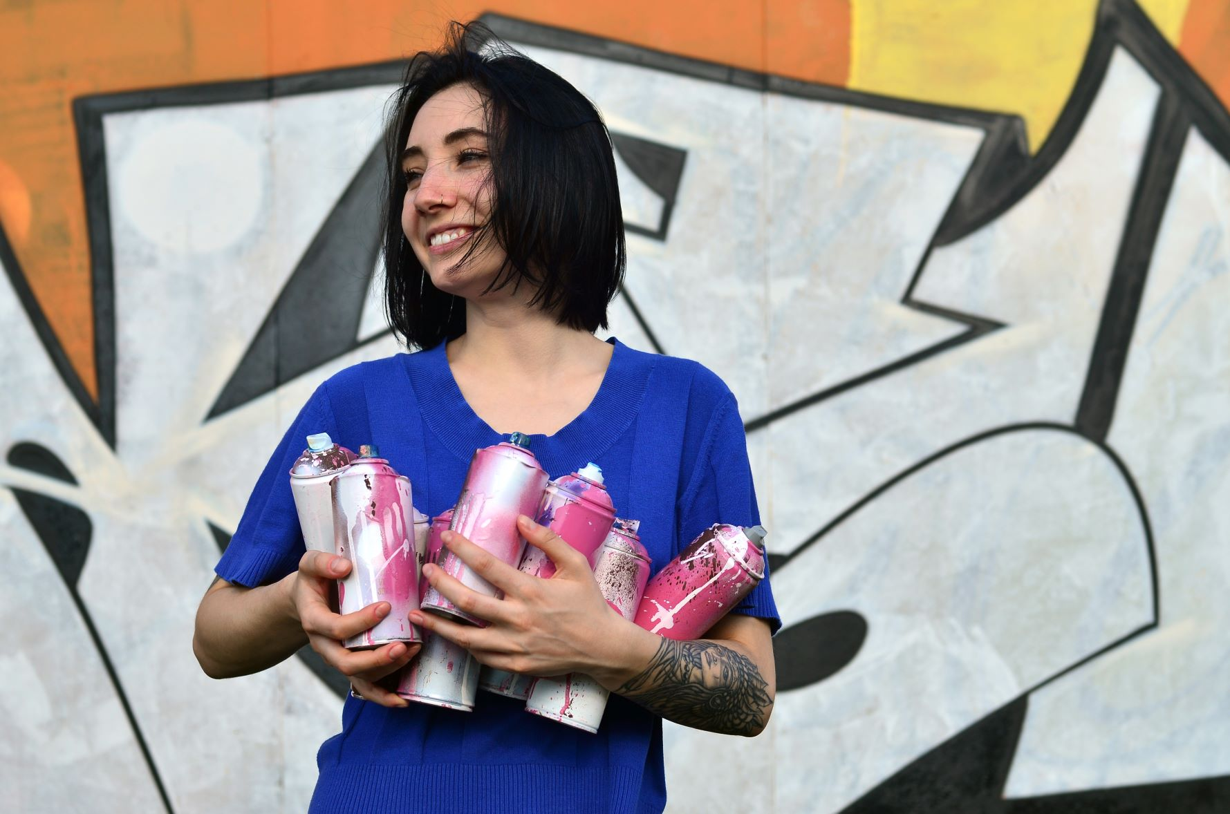 Woman holding aerosol spray paint cans
