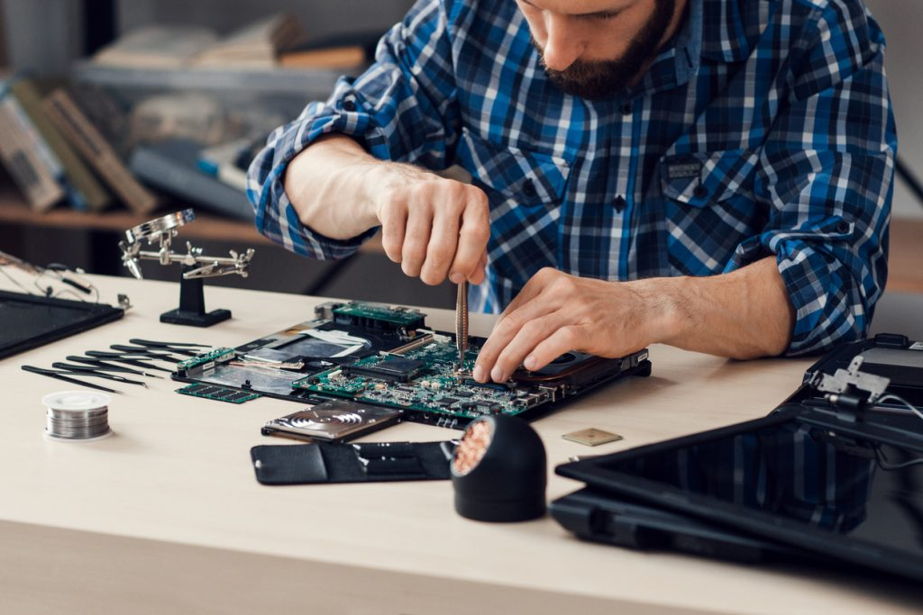 Laptop disassembling with screwdriver at repair shop. Engineer fixing broken computer motherboard in order to recycle old electronics