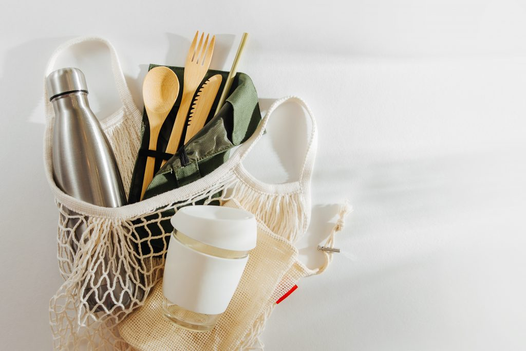 Mesh market bag with bamboo cutlery, reusable coffee mug  and  water bottle. Sustainable lifestyle.  Reduce Plastic Waste concept.