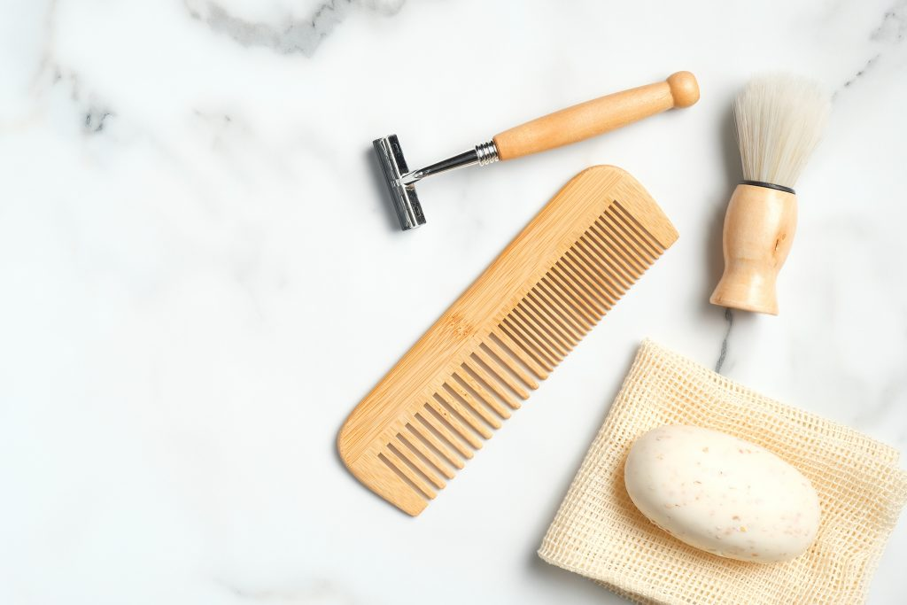 Eco-friendly wooden shaving accessories for man on marble table. Flat lay, top view. Reduce plastic waste concept