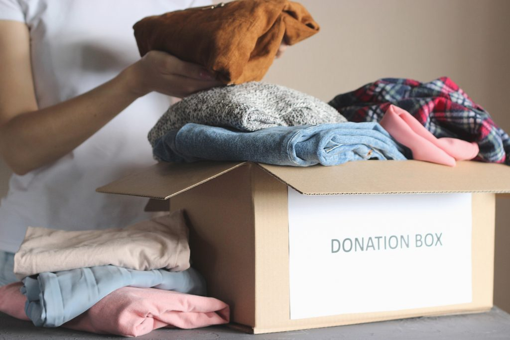 clothes being placed in a donation box