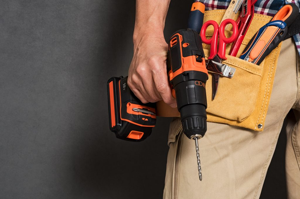 man with toolbelt and power tool