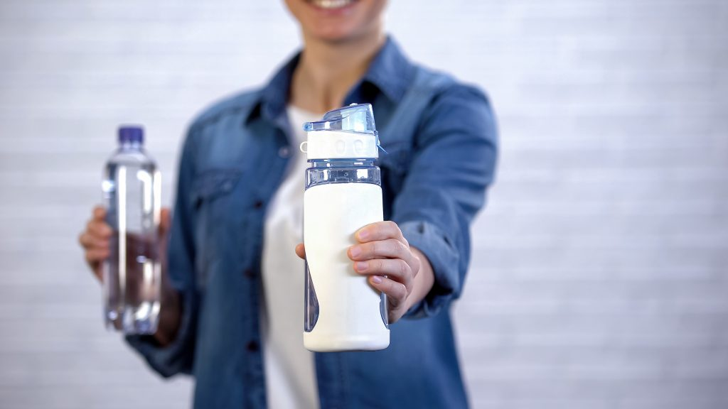 woman choosing a reusable water bottle instead of a disposable plastic water bottle