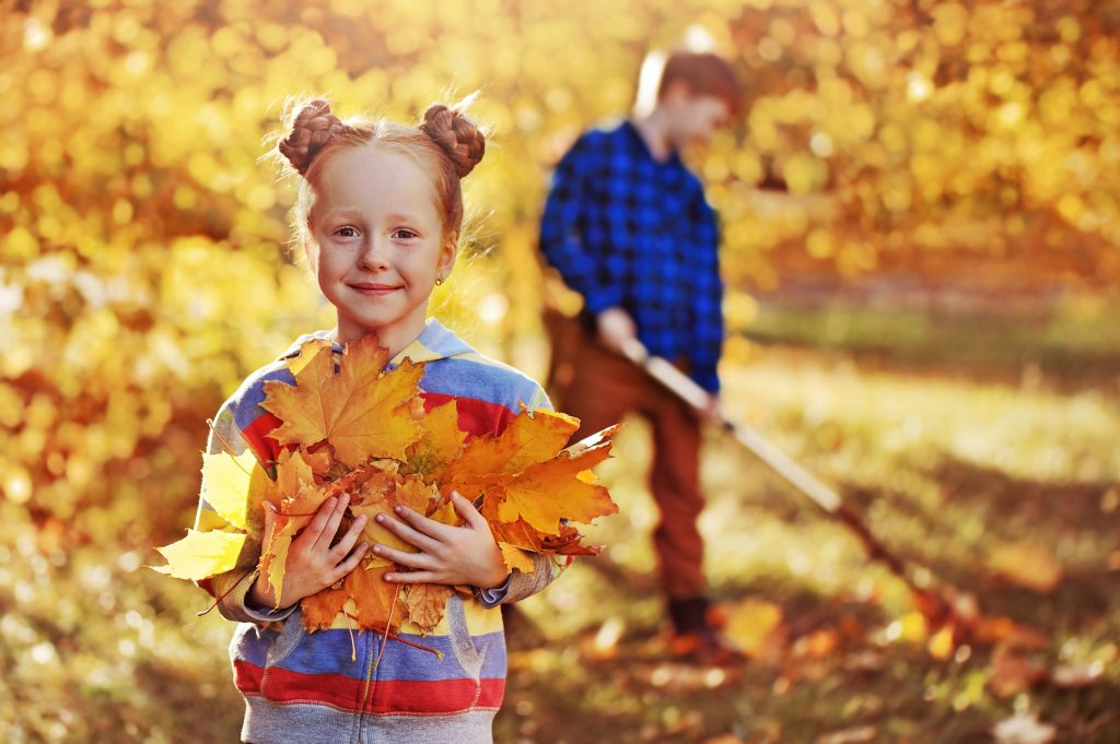 girl holding leaves to add to pumpkin compost