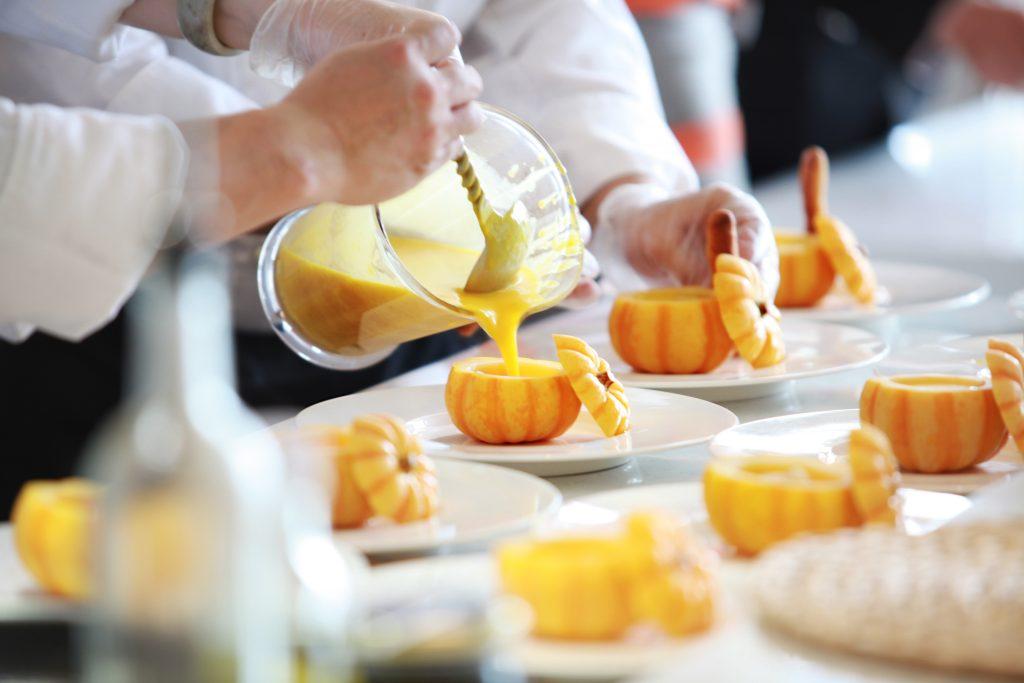 pumpkin soup being served in mini pumpkins